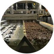 Het gesorteerde materiaal – zink (links) en de fractie koperrijk - komt uit de machine.